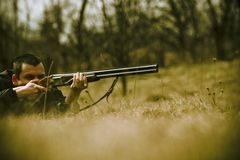 Hunter Aiming Shotgun. Male hunter taking aim with shotgun in a wooded field landscape stock photos