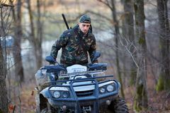 Hunter on ATV in the forest. Young hunter on a quad bike searching for game in the forest Stock Image