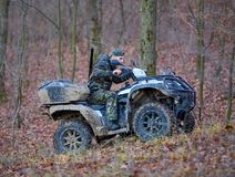 Hunter on ATV in the forest. Young hunter on a quad bike searching for game in the forest Royalty Free Stock Image
