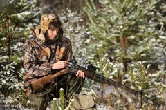 Hunter with a backpack and a hunting gun in the winter forest. Man is charging a hunting rifle. Winter snow-covered forest royalty free stock photos