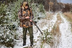 Hunter with a backpack and a hunting gun in the winter forest. Man is charging a hunting rifle. Winter snow-covered forest Stock Photography