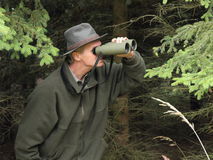 Hunter with binoculars. A male hunter camouflaged in the forest holds a pair of binoculars to his eyes Stock Image
