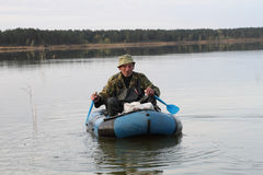 Hunter in a boat. Hunter is floating in an inflatable boat on the lake Stock Images