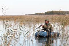 Hunter in a boat. Hunter in an inflatable boat reloads gun Stock Photo