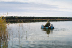 Hunter in a boat. Hunter is floating in an inflatable boat on the lake Stock Image