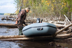 Hunter with the boat on the river. Hunter pulls the boat on the water Stock Images