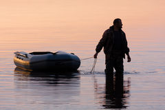 Hunter with boat. Silhouette of the hunter with rubber boat Stock Image