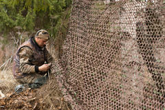 Hunter and camouflage netting Stock Image