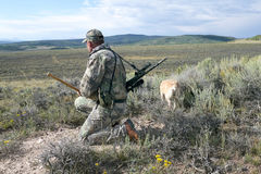 Hunter in camouflage scanning an arid landscape. A hunter with a rifle, hunting dog and wearing camouflage, kneels and scans an arid landscape while hunting Stock Photography