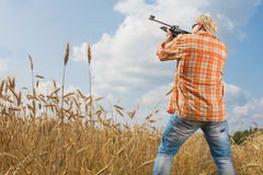 Hunter in cap and sunglasses aiming a gun at field. Hunter at cap and sunglasses aiming a gun at field Stock Image