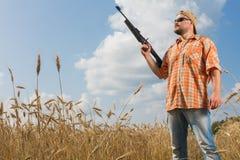 Hunter on cap and sunglasses aiming a gun at field. Hunter at cap and sunglasses aiming a gun at field Stock Photos