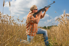 Hunter in cap and sunglasses aiming a gun at field Royalty Free Stock Photos