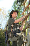 Hunter climbing with hearing protection a high seat Stock Photography