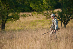 Hunter in countryside. Hunter or soldier in khaki clothing and cap with gun Royalty Free Stock Photos