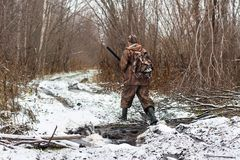 Hunter with hunting gun crosses stream in winter. Hunter crosses stream on the forest road in winter royalty free stock photos