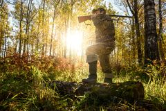 Hunter at dawn. A hunter with a gun in the forest at dawn Stock Photo