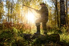 Hunter at dawn. A hunter with a gun in the forest at dawn Royalty Free Stock Photos
