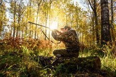 Hunter at dawn. A hunter with a gun in the forest at dawn stock image