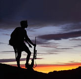A hunter with deer at sunset. A hunter with deer and rifle silhouetted at sunset Stock Photo