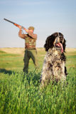 Hunter with dog aiming with his rifle Royalty Free Stock Photo