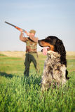 Hunter with dog aiming with his rifle Royalty Free Stock Images