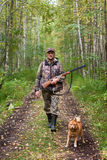 Hunter with dog on the forest road Stock Image