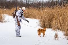 Hunter with a dog on a frozen lake Royalty Free Stock Photography