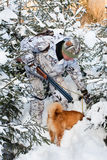 Hunter with dog is looking for a trail in the snow Royalty Free Stock Image