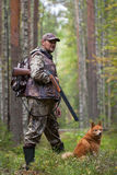 Hunter with a dog in the pine forest Royalty Free Stock Image