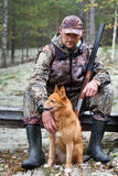 Hunter with a dog sitting in the forest Stock Images