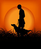 Hunter with dog in the sunset. Kind of Urban Art hunter with dog in the sunset between black and orange color Royalty Free Stock Photos
