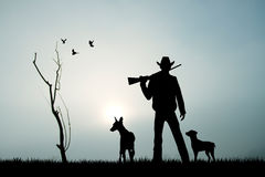 Hunter with dog at sunset Royalty Free Stock Photography