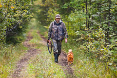 Hunter with dog waiting for prey. Hunter with dog walking on the forest road Royalty Free Stock Image