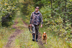 Hunter with dog walking on the road Royalty Free Stock Photos