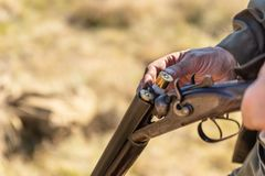 Hunter equips the retro double-barreled shotgun with cartridges, close up. Hunting season royalty free stock images