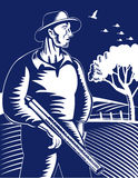 Hunter farmer with shotgun rifle. Vector illustration of a Hunter or farmer carrying a shotgun rifle done in woodcut retro style Stock Image