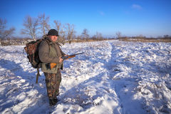 Hunter on field waiting victim. Winter hunting. Royalty Free Stock Photos