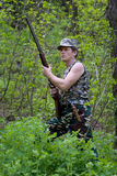 Hunter in forest with gun in hands. Hunter in forest in camouflage with gun in hands stock images