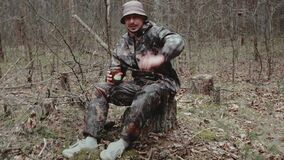 Hunter forest ranger dressed in camouflage suit sits on stump and tells something to camera. Strange correspondent