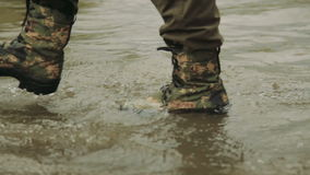 A hunter goes in army boots. A man in army boots. The hunter walks in khaki boots. The soldier overcomes obstacles stock footage