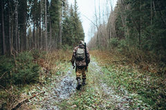 Hunter goes through the forest. Man hunter goes through the forest in rubber boots, with a backpack and a gun. On the ground a little of snow stock images