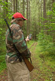 Hunter and GPS. A hunter checks a GPS along a forest road Royalty Free Stock Photo