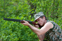 Hunter with gun. Hunter in forest with gun in hand aiming royalty free stock photo