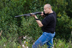 Hunter with a gun in the bushes Stock Images