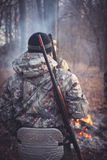 Hunter with gun at campfire in forest during hunting season. View from behind stock images