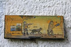 Picture of hunting on the piece of wood. Hunter with gun, dog barking, bear and bees next to their beehives. All on the wooden piece, painted in yellow colours royalty free stock photo