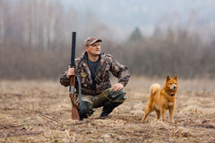 The hunter with a gun and a dog. The hunter sits with a dog on the field and look out for duck Stock Images