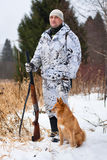 Hunter with gun and dog in winter. Hunter in camouflage with gun and dog in winter royalty free stock photos