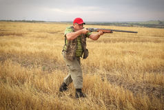 Hunter with a gun on the field Royalty Free Stock Images