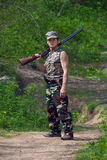Hunter with gun in hand. Hunting man in the forest stock image